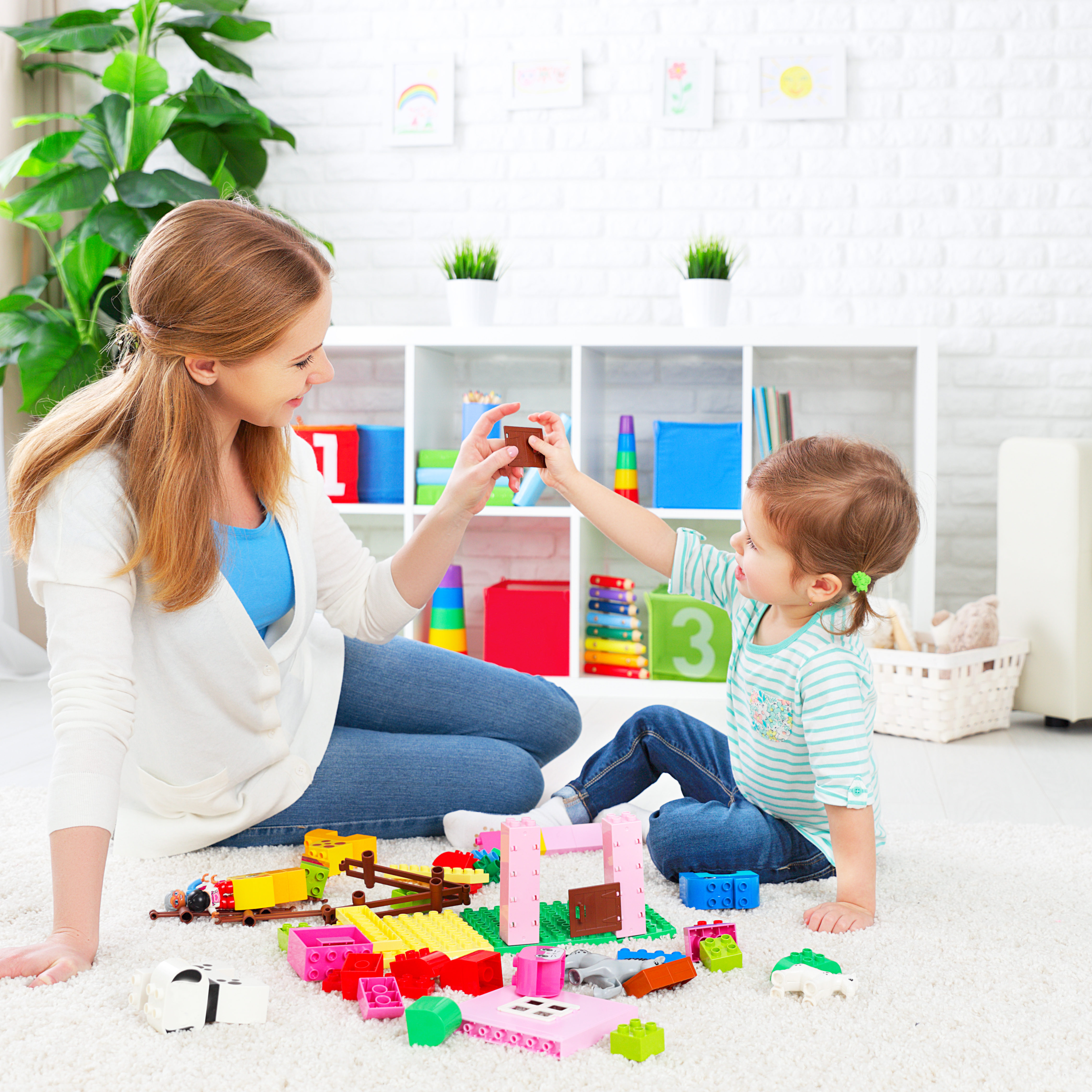 Mother and child daughter playing together, build from the constructor