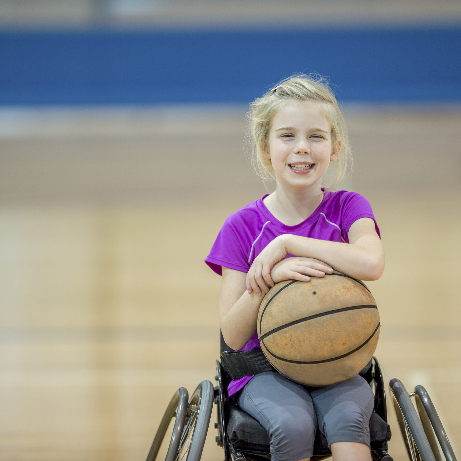 A little girl with a physical disability is playing basketball in her wheelchair.